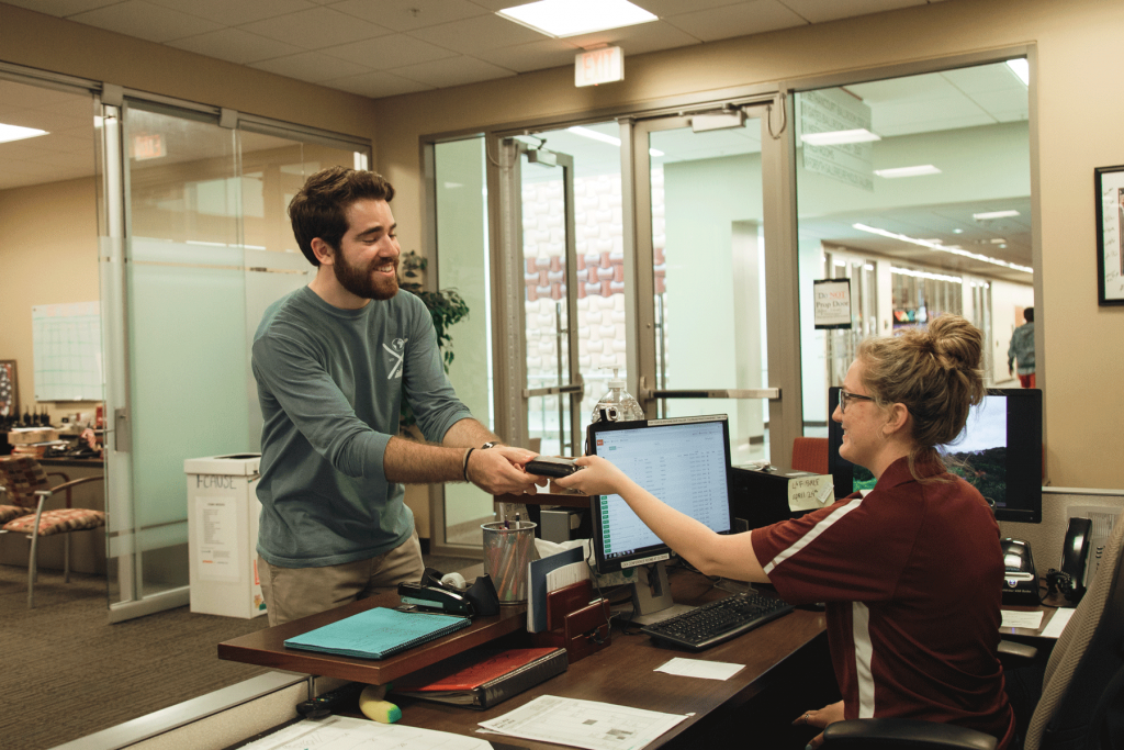 Male student receives his lost wallet from the MSC Student worker.