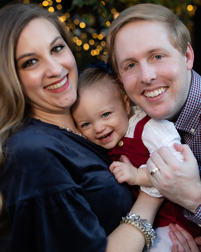 Tyler smiling and posting with his wife and daughter.