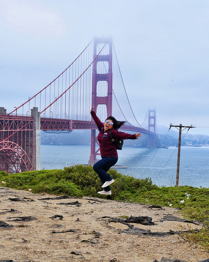 Angelica jumping in front of the golden gate bridge.